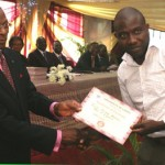 Pro-Chancellor, Deacon Gamaliel Onosode presenting a certificate to one of the beneficiaries.