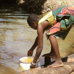 Nigerian woman fetch water from a local pond, which is  a source of drinking water making her susceptible to Guinea worm larvae infestation. Photo by E. Staub, courtesy of the CDC and The Carter Center.
