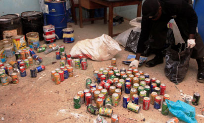 File photo: Policemen from bomb disposal unit  packing defused home made bombs made from cans of soft drinks.