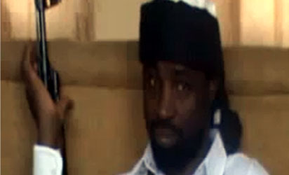 Abubakar Shekau, the leader of Nigeria's Boko Haram Islamist militants, dressed in a black turban and a white gown and bullet-proof vest - holding an AK 47 rifle. In his 40-minute audio message, Shekau reportedly  blamed the deaths of &quot;innocent civilians&quot; on Nigeria's security forces but threatened to carry out a bombing campaign against Nigeria's secondary schools and universities - unless security forces stopped what he claimed was a series of recent attacks on Islamic schools or madrassas in the northern town of Maiduguri.AFP PHOTO / YOUTUBE