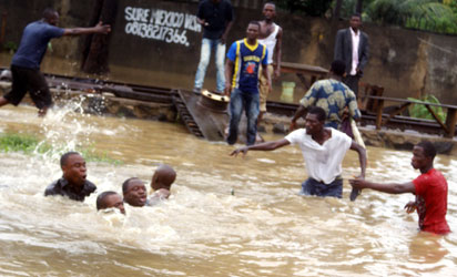 Lagos yesterday — : Rescue bid almost turned tragic in Shogunle as flood sweeps Lagos