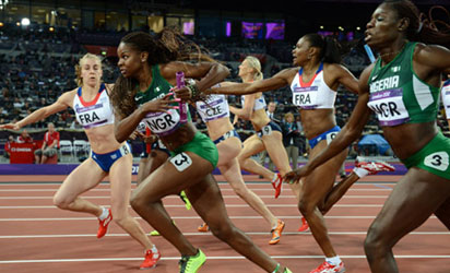 Nigeria&#8217;s Ajoke Odumosu (R) hands the baton to Regina George as they compete in the women&#8217;s 4X400 relay final of the London 2012 Olympic Games in London. PHOTO - AFP.