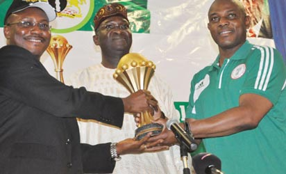 PRESENTATION... The Super Eagles were hosted by the Lagos State Governor, Babatunde Fashola yesterday. Seni Adetu, MD/CE Guinness Nigeria Ltd[left] and Coach  Stephen Keshi (right), presenting the trophy to Gov. Fashola during the reception held at Lagos House, Alausa, Ikeja. Photo: Bunmi Azeez