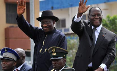 Nigerian President Goodluck Jonathan (L) and his Ivorian counterpart Alassane Ouattara wave to the crowd on March 1, 2013 during a visit to Yamoussoukro. Goodluck Jonathan is on a two-day official visit to Ivory Coast. AFP PHOTO