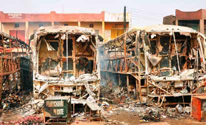 Burnt luxury buses lie in the parling area at New Road bus station in Sabon Gari district in northern Nigerian's largest city of Kano on March 19, 2013. Two suicide bombers rammed their car into a bus laden with passengers at the motor park, killing at least more than 22 people and injuring 65 others, and the  following explosion burnt five buses. AFP PHOTO