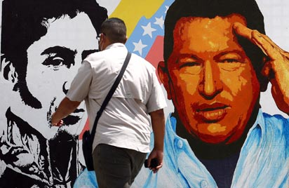 TOPSHOTS - A man walks past a mural portraying the Venezuelan flag, President Hugo Chavez and South American liberator Simon Bolivar at the 23 de Enero neighbourhood, in Caracas on March 5, 2013. AFP PHOTO