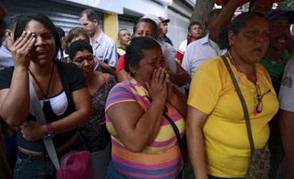 Supporters of Venezuelan President Hugo Chavez cry after knowing of his death in Caracas on March 5, 2013.  AFP  Photo.