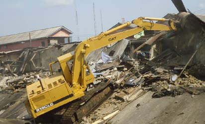 bulldozer demolishing illegal structures at Ladipo