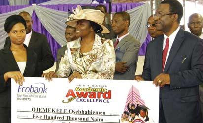 Pastor Shade Olukoya and Prof. Akin Osibogun presenting cheque to Miss Ojemekele Osebhahiemen at the award ceremony.