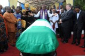 "Anglican priest Owen Nwokolo prays in front of the coffin bearing the body of late Nigerian writer Chinua Achebe upon arrival at Abuja airport, on May 21, 2013. The body of Achebe, the author of internationally acclaimed novel ""Things Fall Apart"" and a towering figure in African literature, arrived in Abuja two months after his death in a US hospital. He is due to be buried in his native town of Ogidi on May 23, 2013. AFP PHOTO/PIUS UTOMI EKPEI"