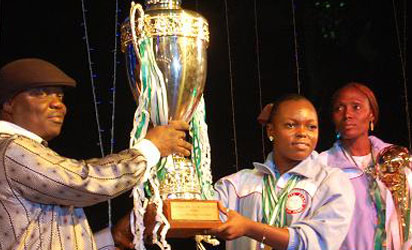 RECEPTION: Team Delta Captain Ruth Izenegu presenting the overall winners trophy to Governor Emmanuel Eweta Uduaghan Tuesday night in Asaba during the reception for the victorious Delta athletes. Uduaghan himself also received an award from Delta State Sports Commission's Amaju Pinnick for his support for sports in the state.Photo: Henry Unini .